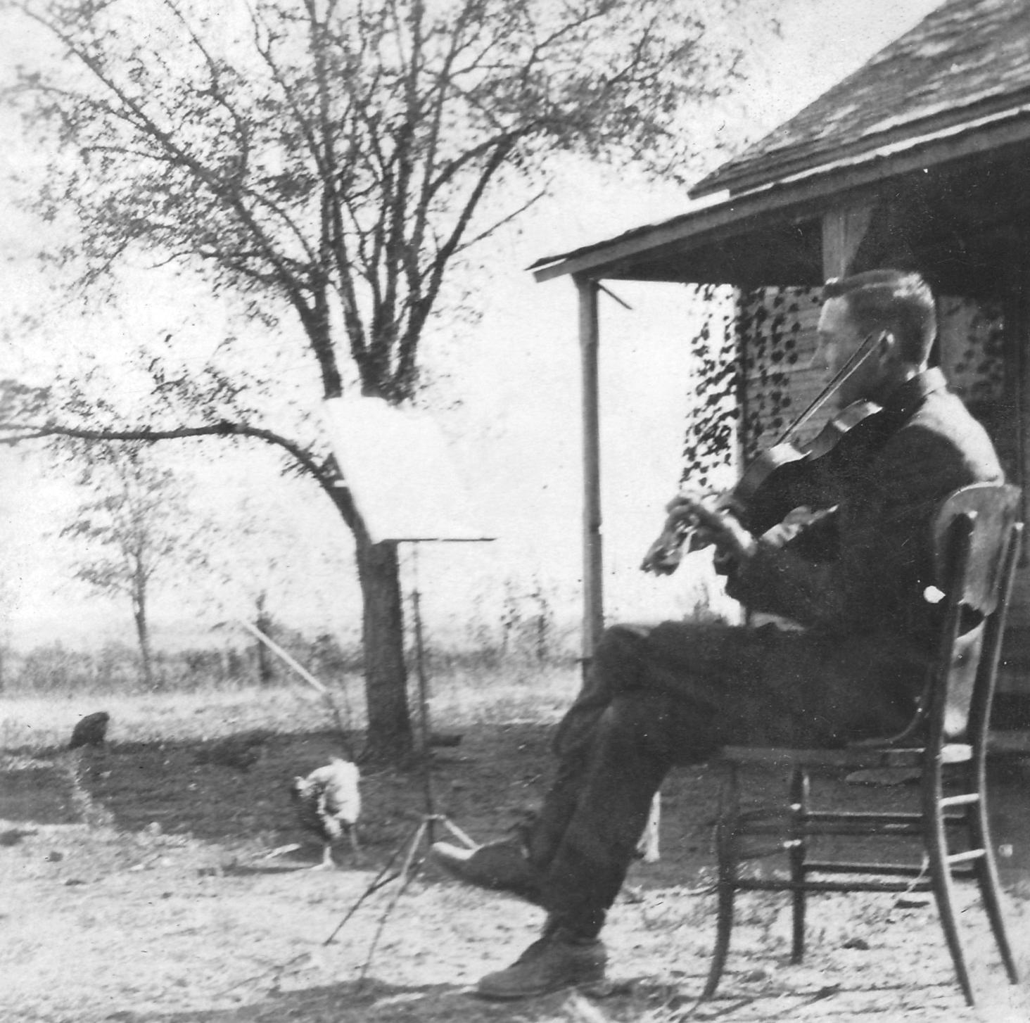 "Tom initially taught himself to play by ear, but he was proud when he learned to play ""by note"" in the early 1920s. Note the music stand and the chickens"